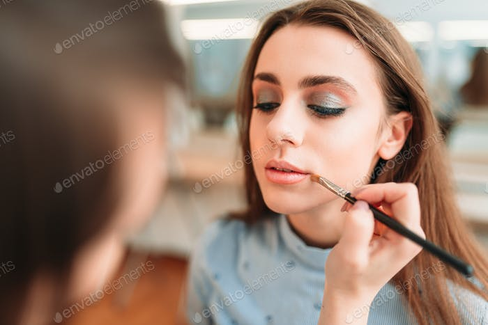 Make up artist hand applying gloss on woman lips