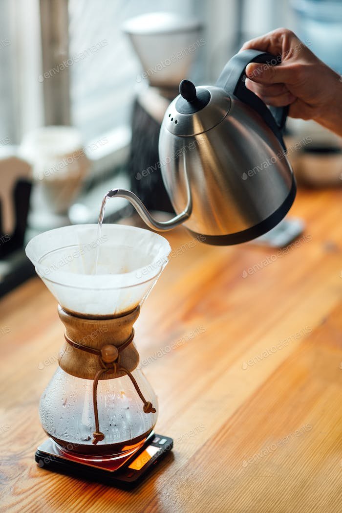 brewing coffee by an alternative method, pouring boiling water from a teapot into a filter