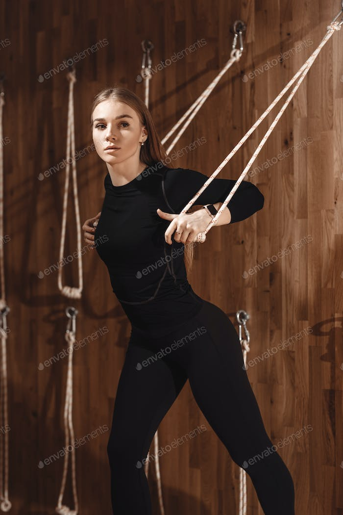 Slim young girl dressed in a black sportswear is doing stretching on special rope equipment in the