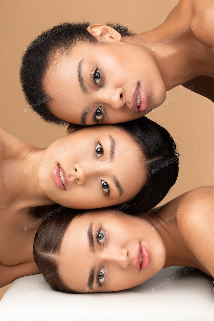 Portrait Of Three Attractive Women Looking At Camera, Beige Background