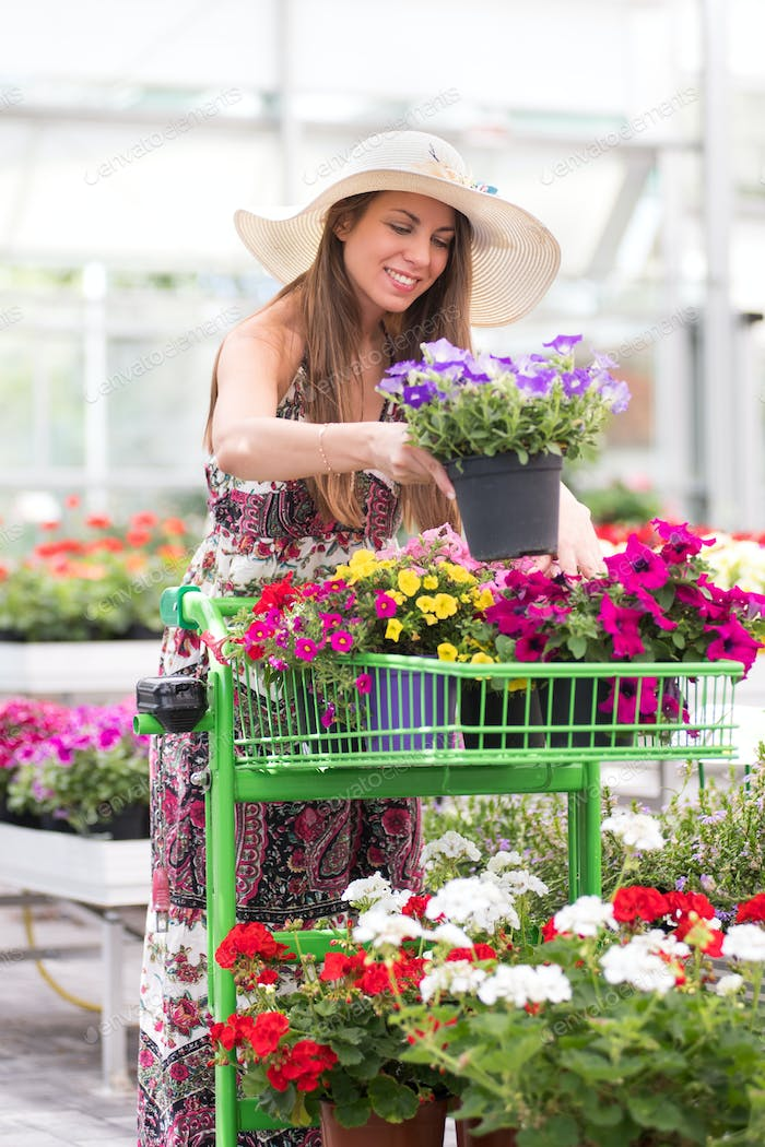 Stylish young woman choosing plants at a nursery