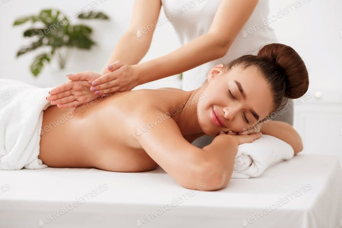 Body care. Relaxed woman enjoying back massage