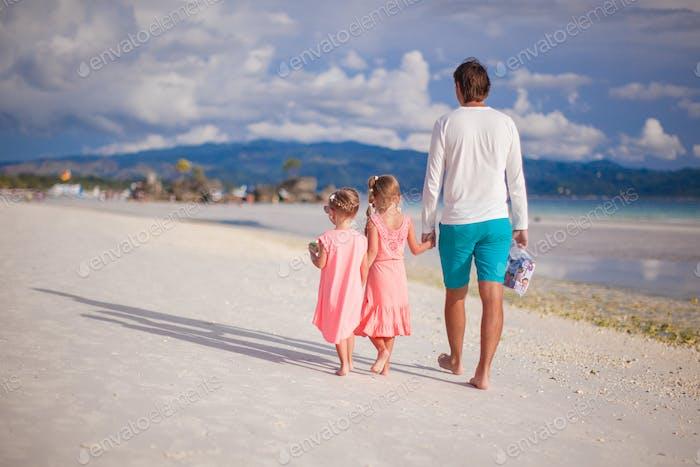 Entzückende kleine Mädchen und junger Vater am tropischen weißen Strand