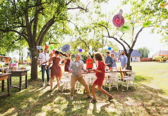 A senior couple and family dancing on a garden party outside in the backyard.
