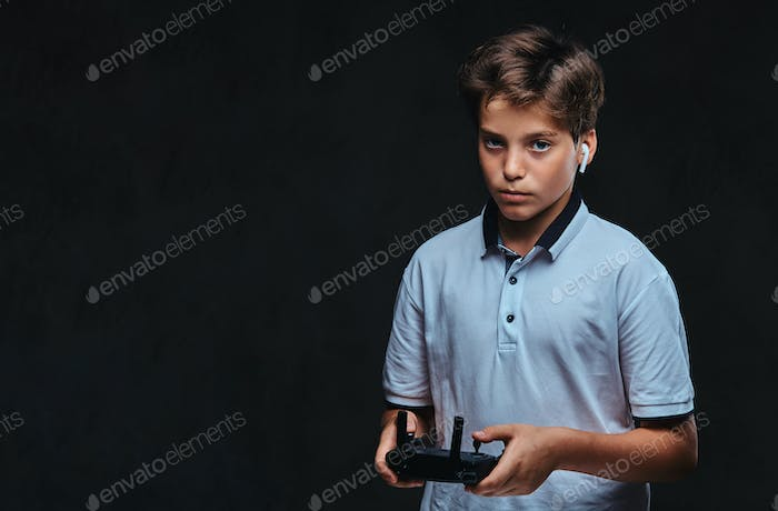 Young boy dressed in a white t-shirt holds a control remote