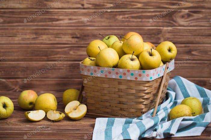 Goldene Äpfel in einem Korb auf einem hölzernen Hintergrund