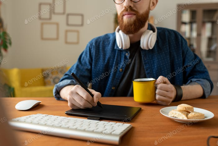 Young creative web designer in casualwear having coffee with cookies and drawing