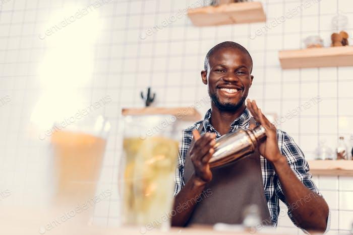lächelnd gutaussehend Afroamerikanischer Barkeeper machen Cocktail in Shaker auf der Bar Theke