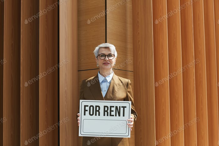 Real estate agent with placard outdoors