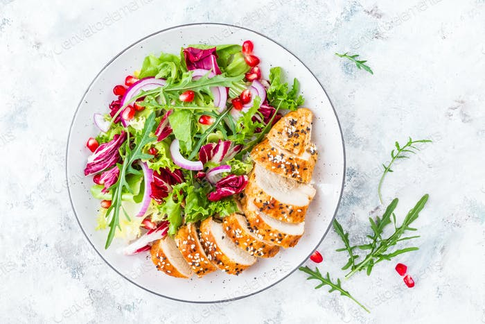 Grilled chicken breast, fillet and fresh vegetable leafy salad with arugula and pomegranate
