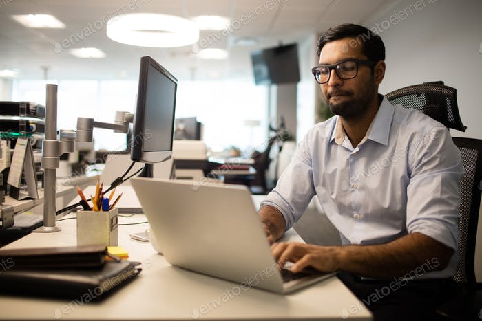 Concentrated businessman working on laptop in office