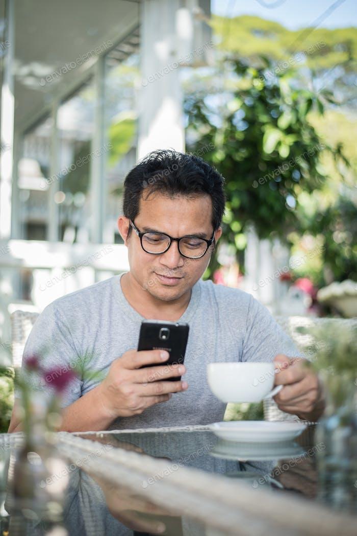 Hombre guapo usando el teléfono móvil en el café