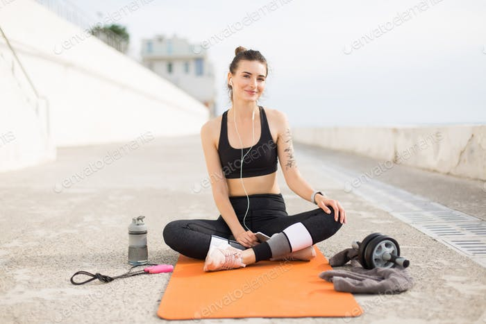 Young smiling woman in sporty top and leggings with earphones ho