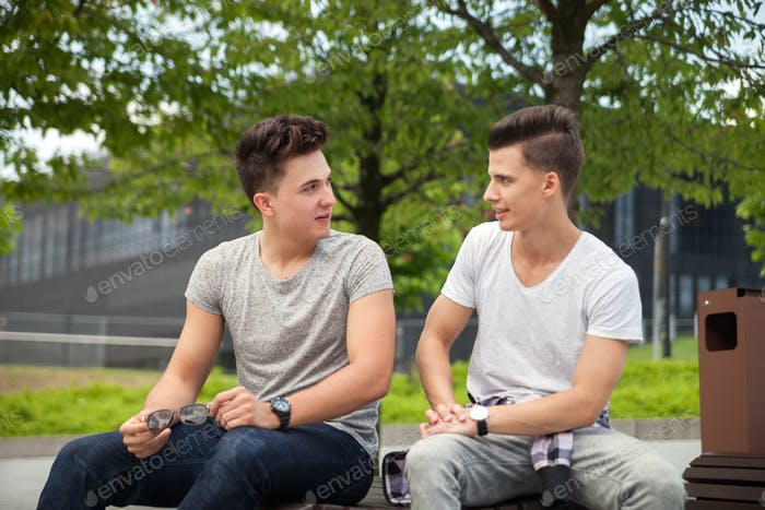 Two friends sitting on bench in town and talking, best friend
