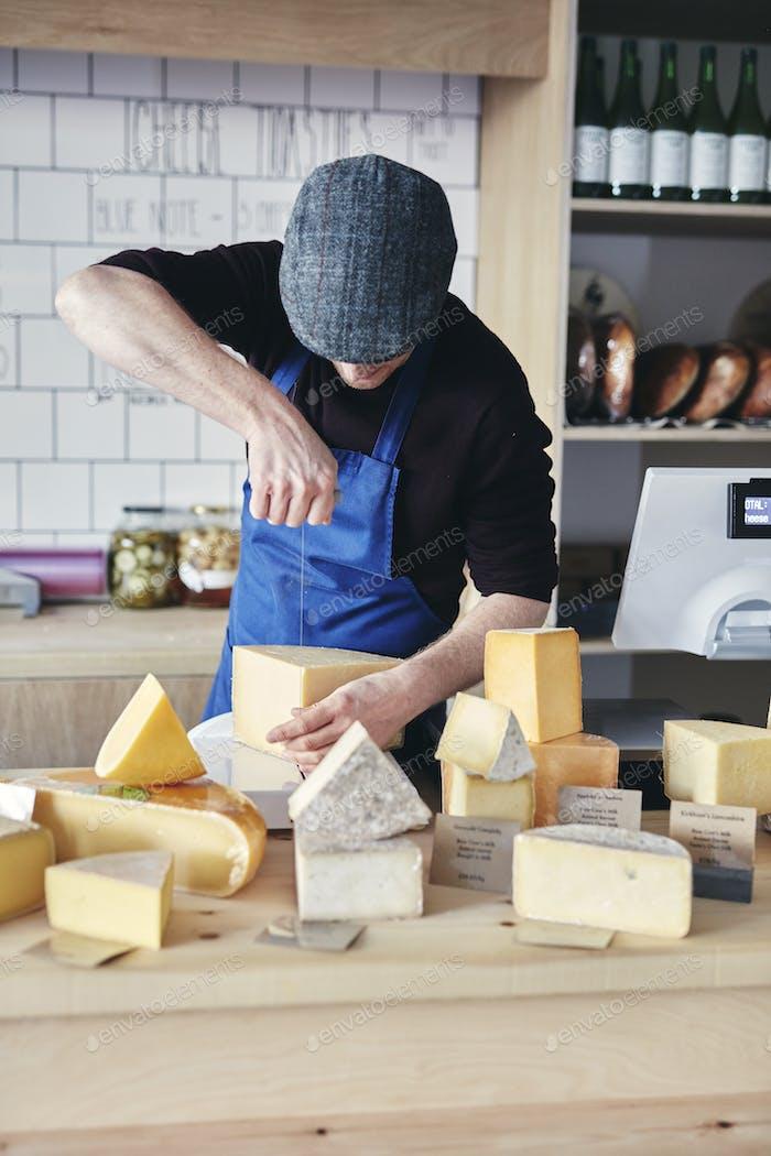 Cheesemonger cutting cheese using cheese wire