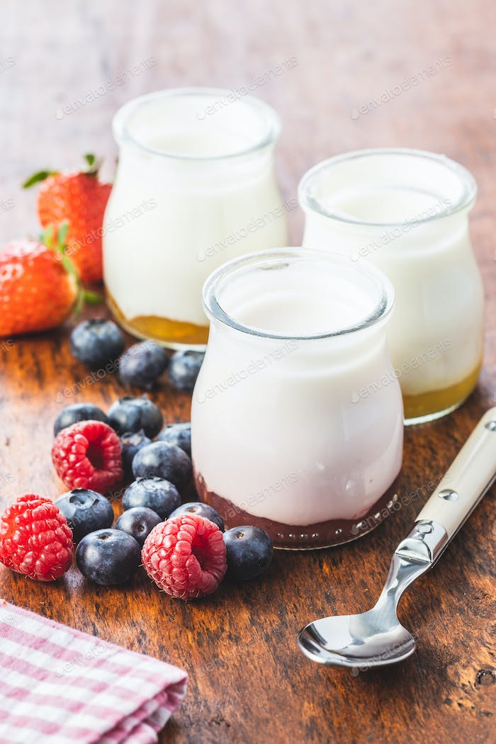 White fruity yogurt in jar and blueberry, raspberry, strawberry