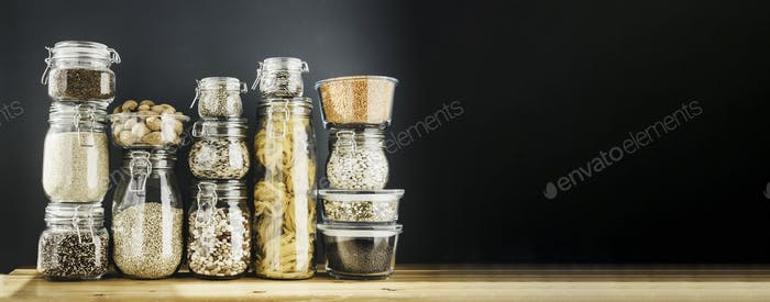 Thumbnail for Banner with assortment of uncooked grains, cereals and pasta in glass jars on wooden table. Healthy