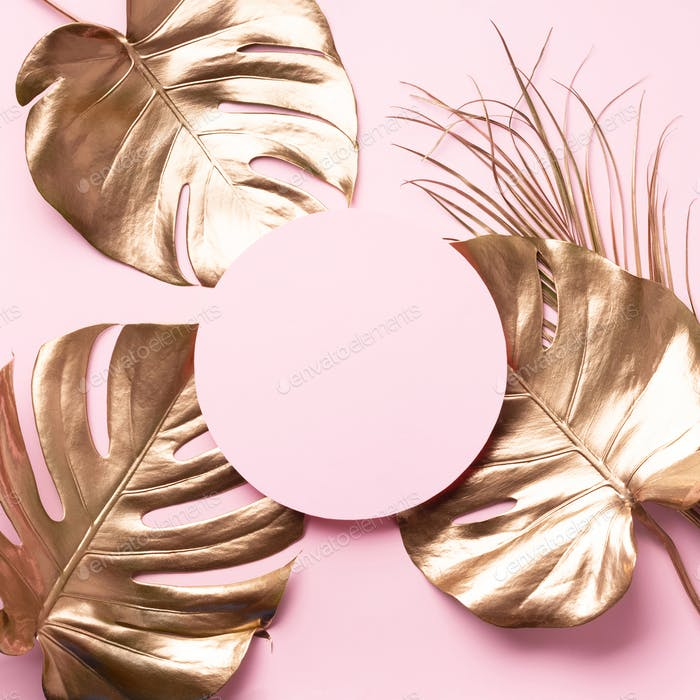 Exotic summer trend in minimal style. Golden tropical palm and monstera leaves on pastel pink color