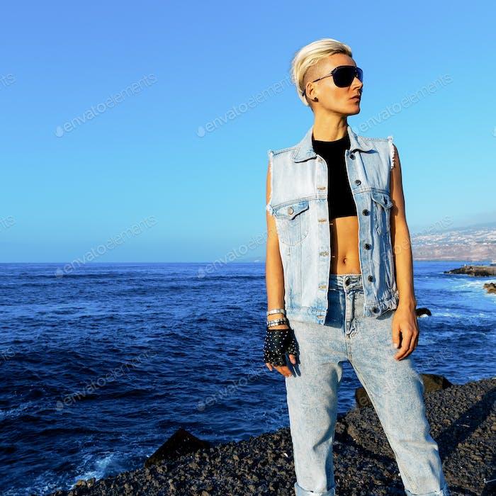 Stylish blonde in denim otffit on background ocean