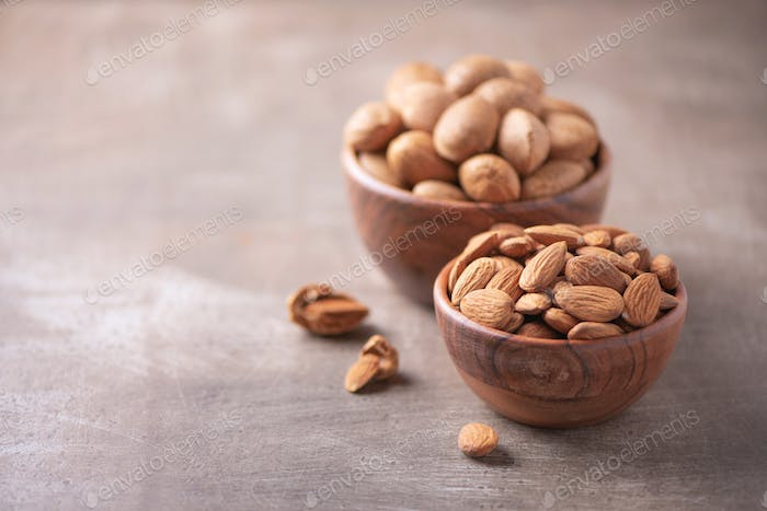 Almond nuts in wooden bowl on wood textured background. Copy space. Superfood, vegan, vegetarian