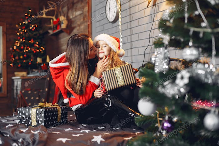 Mother in a santa's suit with cute daughter at home