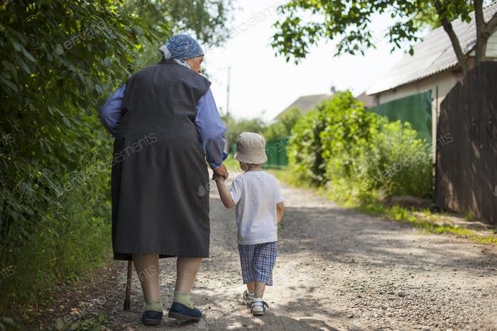 Great grandmother and toddler boy walking down street in countryside