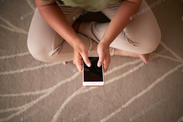 Crop woman using smartphone on floor