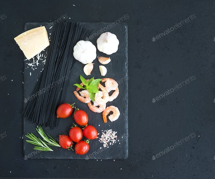 Ingredients for black pasta with seafood. Shrimps, spaghetti, basil, garlic, spices, parmesan cheese