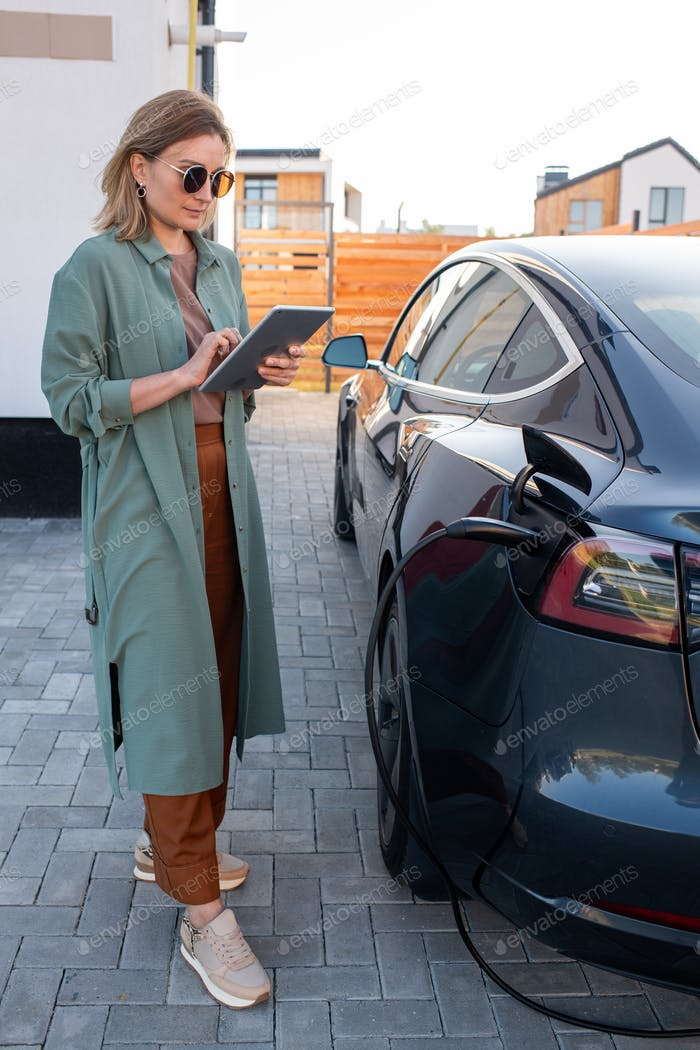 Young elegant businesswoman charging her car and networking