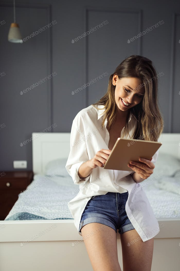 Attractive young woman using digital tablet and relaxing