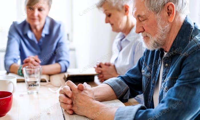 Старшие люди в группе чтения Библии в клубе сообщество центра