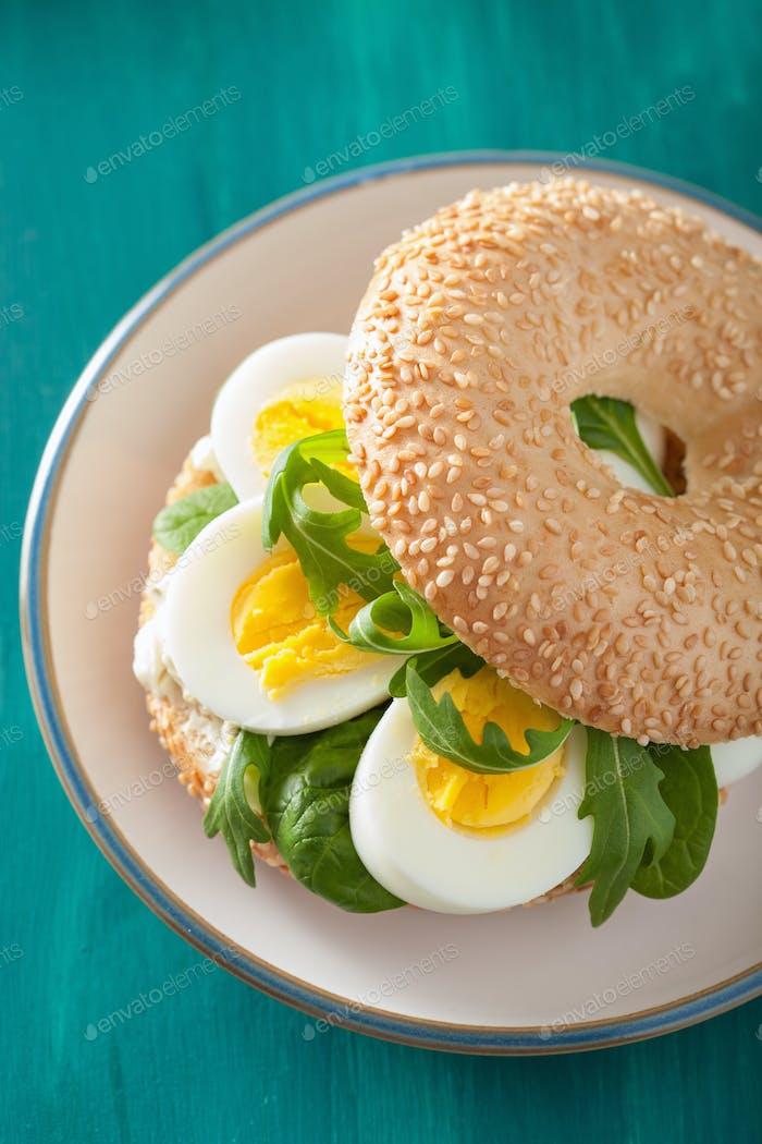 Frühstückssandwich auf Bagel mit Eierrahmkäse Rucola