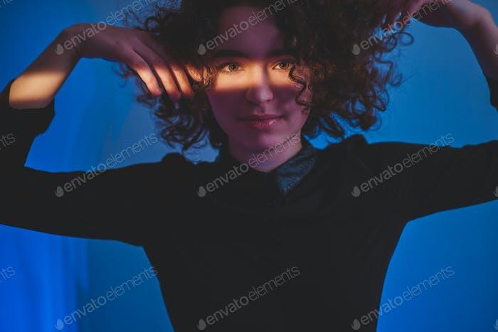 Lockige Frau mit Streifen von Licht auf dem Gesicht