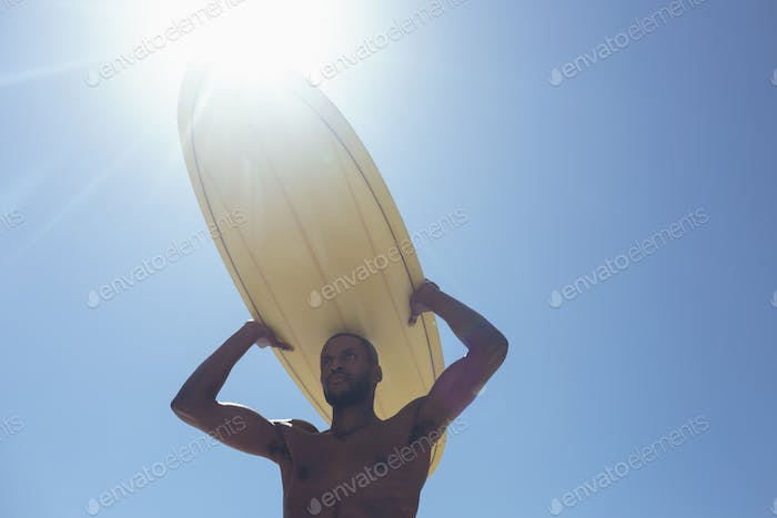 Male surfer carrying surf board at beach