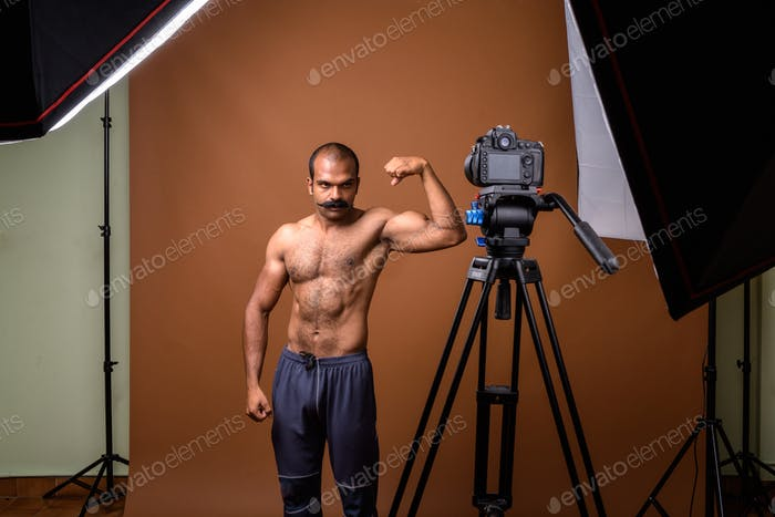 Portrait of muscular Indian man with mustache shirtless vlogging with camera
