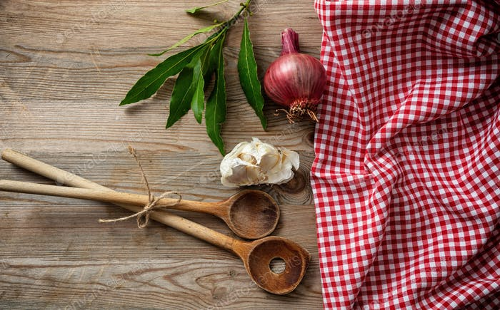 Wooden kitchen utensils, herbs and red tablecloth on wooden table, top view, copy space