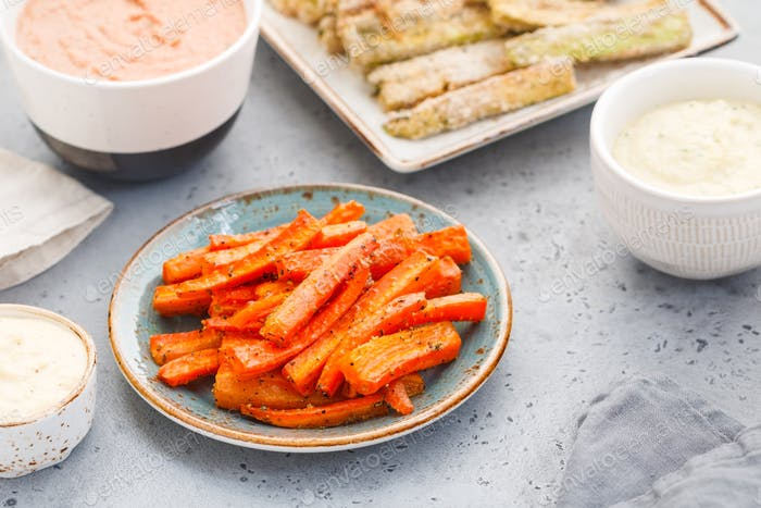 Baked season carrot sticks with sauce and hummus on a dinner table. Vegetarian healthy food.