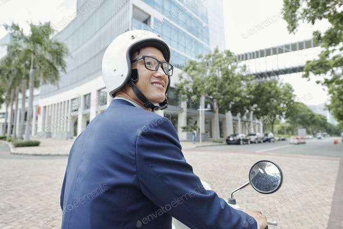 Happy businessman riding scooter