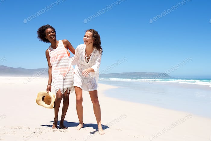 Smiling women walking together at the seaside