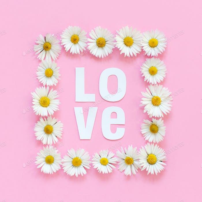 Rechteckiger Blumenrahmen und Text LOVE auf hellrosa Hintergrund