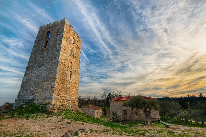 One tower, two houses in Chalkidiki with clouds and sun