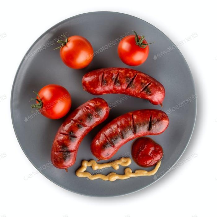 Жареные колбаски с кетчупом на тарелке