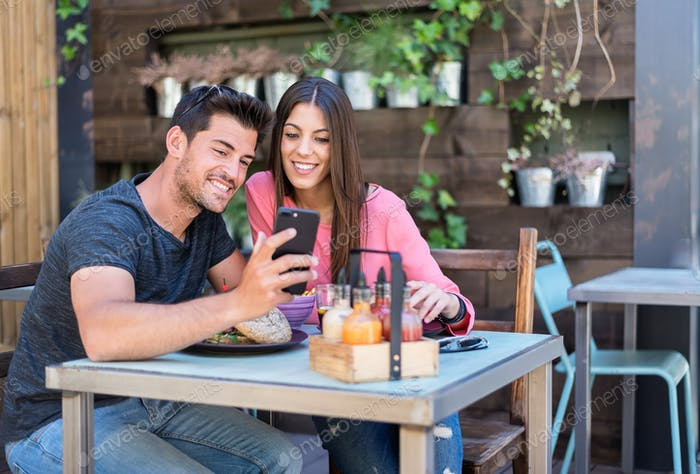Happy young couple seating in a restaurant terrace with a smartp