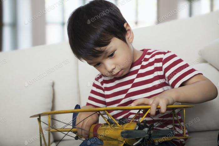 Kleiner Junge nach unten schauen und halten ein Modellflugzeug, auf der Couch im Wohnzimmer