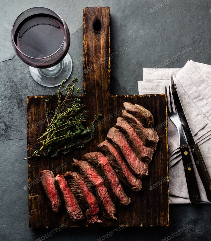 Medium rare beef steak on white plate, glass of red wine, slate background