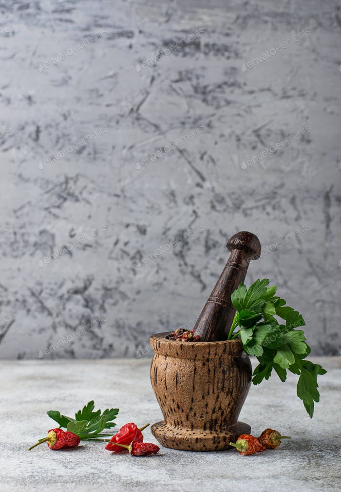 Wooden mortar with pepper and parsley