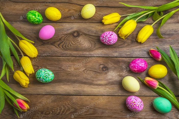Easter rustic background with pink, yellow and green painted egg