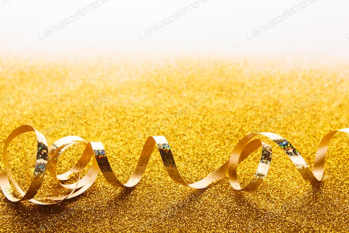 Curly golden serpentine on glitter background