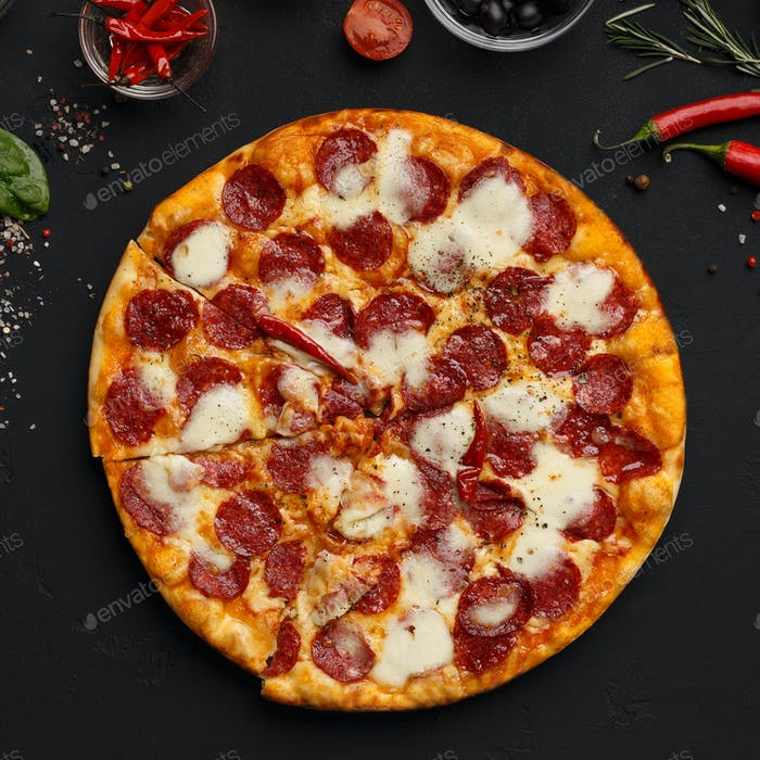 Hot pizza with salami and cheese on black background