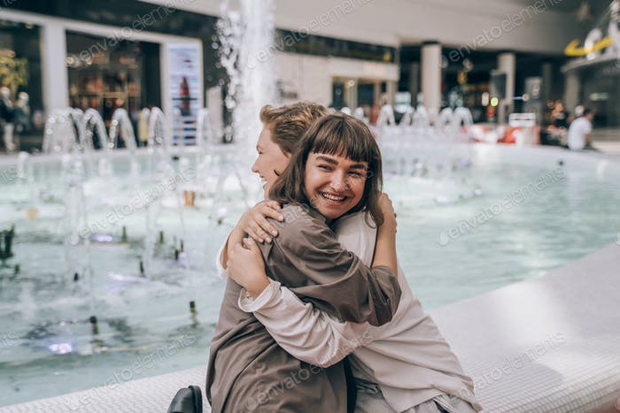 Two girls have fun in the mall, a fountain in the background
